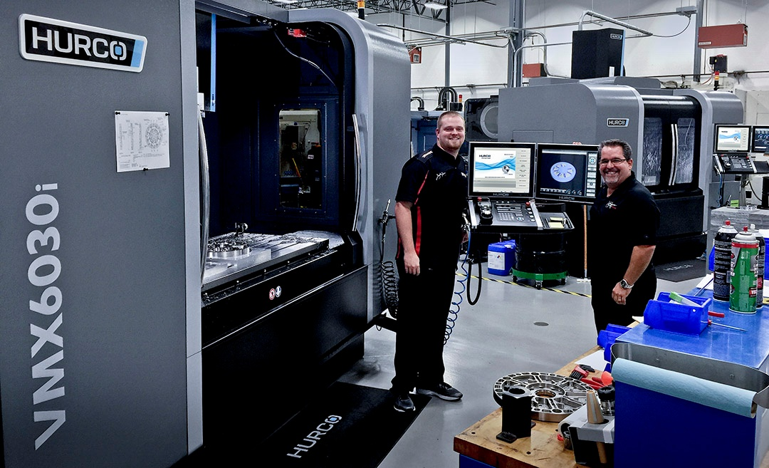 employees at john force racing in front of their Hurco VMX6030i CNC machining center